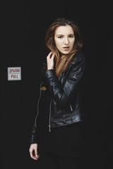 Ginger female model posing against black wall