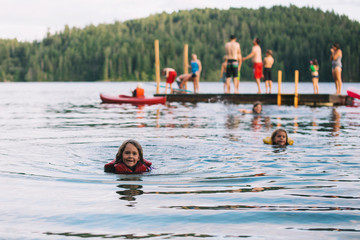 Young girl swimming in lake with lifejacket