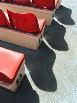 Rows of red seats with long shadows