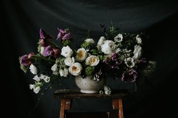 Dark and moody purple and white wedding flower arrangement with dark background