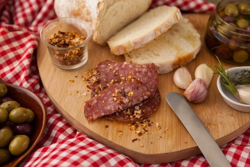 Chili flakes on meat by bread with olives in jar