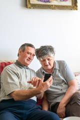Elder couple using a smartphone together