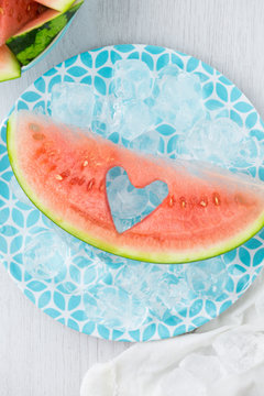 A slice of watermelon  on ice with a heart shape cut out