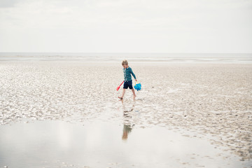 Little boy walking on the beach