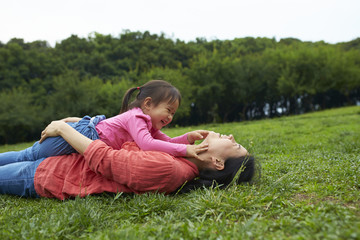 happy little asian girl playing with her mother outdoor in the park