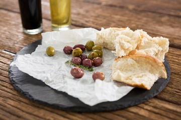 Marinated olives and bread slices kept on tray