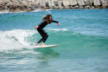Long-haired bearded surfer riding wave