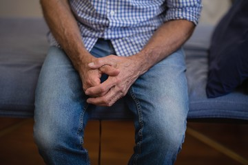 Midsection of senior male patient sitting with hands clasped on