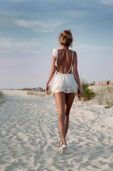 Girl in summer dress standing on a beach and looking to the sea