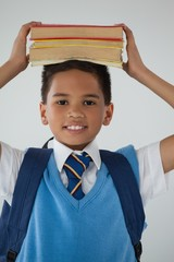 Schoolboy holding books on his head against white background