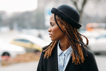 Fashion pedestrian. Young African American girl. Stylish model in selective focus outdoors, beauty concept