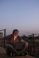 Happy social media communication on roof. Smiling male freelancer with laptop outdoors in focus on foreground. Urban background with free space, creative self-education