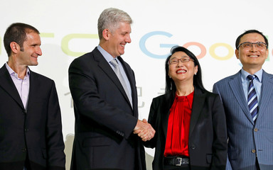 Google hardware executive Rick Osterloh (2n-L) shakes hand with HTC CEO Cher Wang during a news conference to announce Google to acquire HTC's Pixel smartphone division, in Taipei