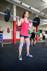 Determined Female Lifting Heavy Barbell