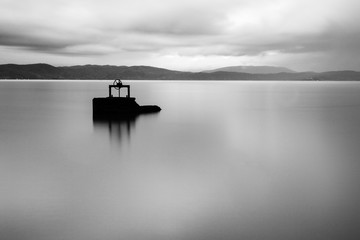 Long exposure view of a lake at dusk, with an old winch in the midst of water