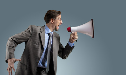 Businessman in gray suit with megaphone