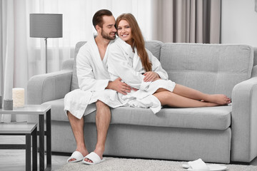 Young loving couple in bathrobes sitting on sofa at home