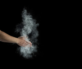 Freeze motion of dust explosion in hands isolated on black background