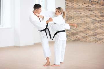 Young man and woman practicing karate in dojo
