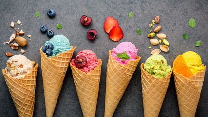 Various of ice cream flavor in cones blueberry ,strawberry ,pistachio ,almond ,orange and cherry setup on dark stone background . Summer and Sweet menu concept.