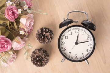 alarm clock with pine cone and rose on wood table with copy space for product display montage.