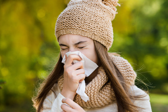 Young woman sneezes in a handkerchief on the street in autumn