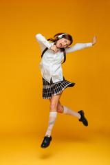 Full length portrait of an excited teenage schoolgirl in uniform