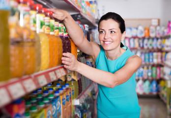 Adult woman in the supermarket choosing juice