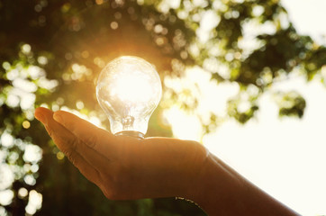 light bulb in hand person with sunset of solar energy cocept