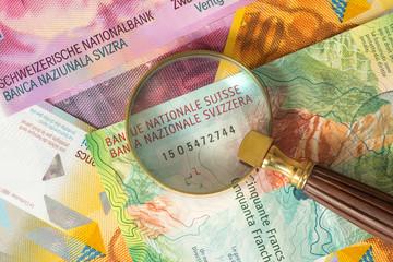 Schweizer Franken und eine Lupe