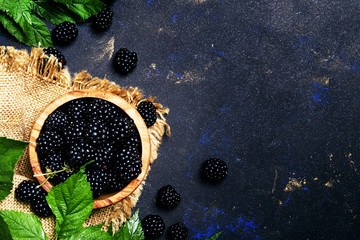 Fresh blackberries in a wooden bowl, black background, top view