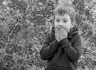 A scared closeup facial expression of a Caucasian child, black and white image. Afraid of punishment, bad behavior, severe punishment, scared kid, caught on lie, overwhelmed child stock image.