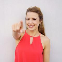 schöne junge frau zeigt mit dem finger nach vorne