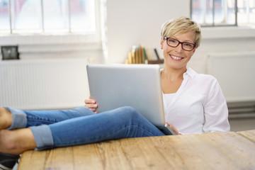 frau sitzt zuhause am tisch und arbeitet entspannt am laptop