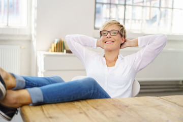 zufriedene frau sitzt zuhause und lehnt sich entspannt zurück