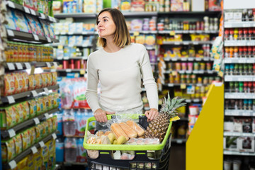 cheerful girl customer looking for food supplies for week in supermarket