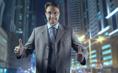 Businessman in gray suit smiling and both thumbs up