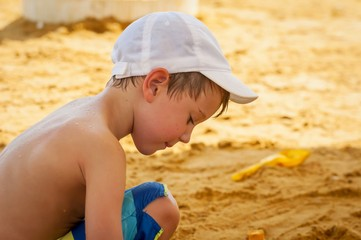 Pretty Caucasian kid playing in the sand at the seaside.