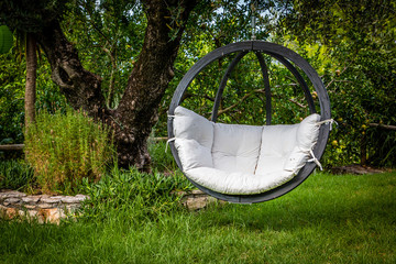 Lounge hanging chair with white pillow in the garden with green nature background