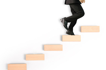 business person stepping up  toy staircase