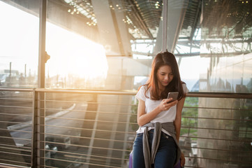 Women are using their smartphones to Flight Checking at airports.airports and technology concept.