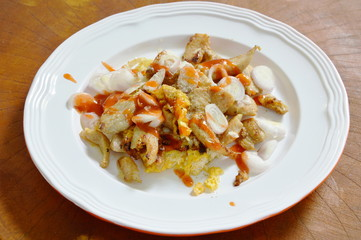 fried chicken with egg topping slice shallot and dressing chili sauce on dish