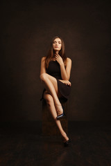 Attractive girl in short dress posing near dark wall
