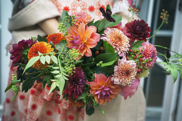 Cadres-photo bureau Dahlia bride in a red lace dress holds a bouquet of dahlias and roses