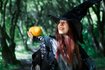Photo of cheerful witch in hat with pumpkin