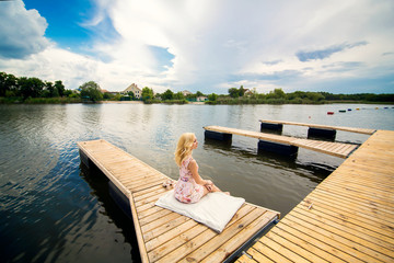 Girl looks at the river sitting on the dock