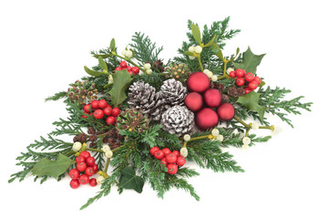 Christmas centrepiece decoration with red baubles, holly, ivy, mistletoe, cedar and juniper leaf sprigs and pine cones on white background.