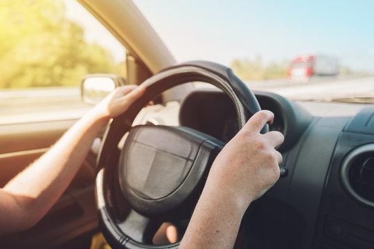 Woman holding on black steering wheel