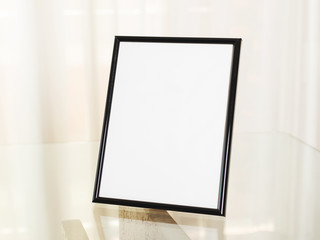 Photo frame on glass table. Portrait.