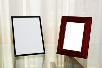 Two picture frames on glass table. Portrait.
